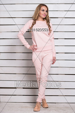 Pretty Young Blond Woman In Pink Clothes Posing Near White Wooden Wall Stock Photo