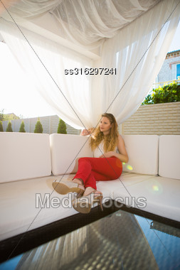 Pretty Young Blond Woman Relaxing In Summer House Stock Photo