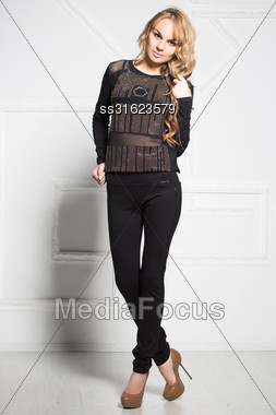 Pretty Young Blonde In Black Clothes Posing Near White Wall Stock Photo