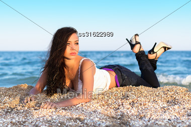 Pretty Young Brunette Lying On The Beach Stock Photo