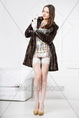 Pretty Young Brunette Posing In Frank Dress, White Stockings And Fur Coat Stock Photo
