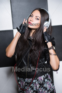 Pretty Young Brunette Posing In The Studio With Headphones Stock Photo
