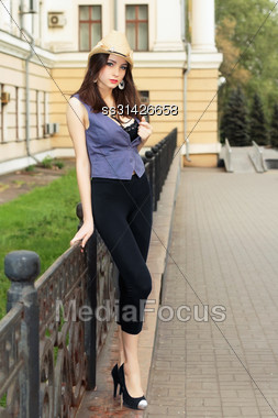 Pretty Young Lady In Black Tight Leggings Posing Near The Metallic Fence Stock Photo
