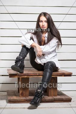 Pretty Young Woman Posing Near White Board Wall Stock Photo