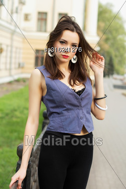 Pretty Young Woman Posing Outdoors In Grey Vest Stock Photo