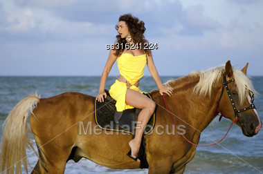 Pretty Young Woman Riding A Horse On The Beach Stock Photo