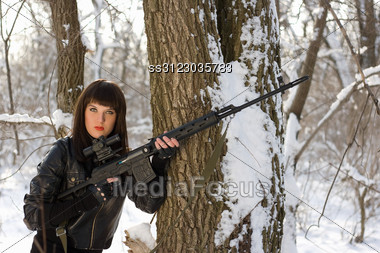 Pretty Young Woman With A Sniper Rifle Near The Tree Stock Photo