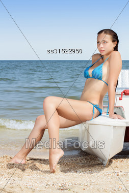 Pretty Young Woman Wearing Blue Swimsuit Posing On The Catamaran Stock Photo
