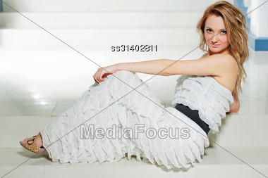 Pretty Young Woman In A White Dress Sitting On The Stairs Stock Photo