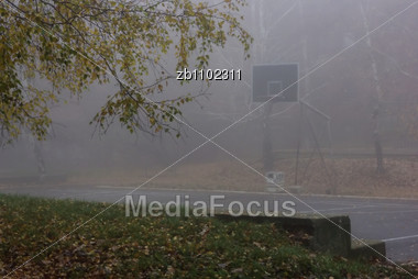 Public Park At Foggy Autumn Day, Empty Basketball Playground, Yellow Leaves Stock Photo