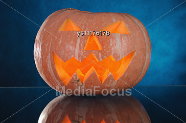 Pumpkin With Lighting Candle Inside On Blue Background Stock Photo