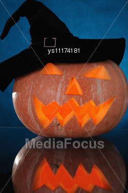 Pumpkin With Lighting Candle Inside On Darck Blue Background Stock Photo