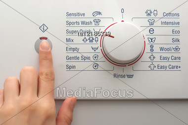 Pushing The Power Button Of Washing Machine Stock Photo