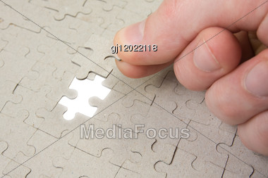 Puzzle Piece Coming Down Into It's Place Stock Photo