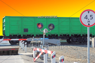 Railroad Cars At The Crossing With A Barrier And A Red Traffic Light. Stock Photo