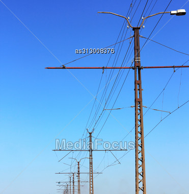 Railroad Railway Catenary Lines Against Clear Blue Sky. Stock Photo
