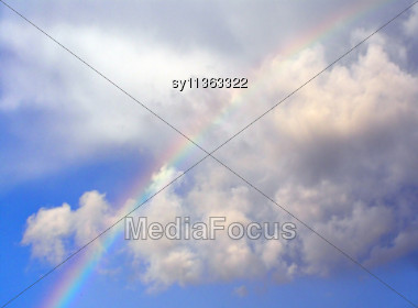 Rainbow In Cloudy Sky Stock Photo