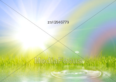 Rainbow The Sun And A Grass Reflected In Water Stock Photo