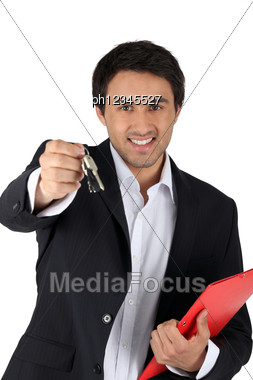 Real Estate Agent Holding Keys And Folder Stock Photo
