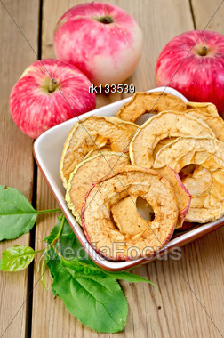 Red Apples Fresh And Dried In A Bowl, Green Leaves Against Wooden Boards Stock Photo