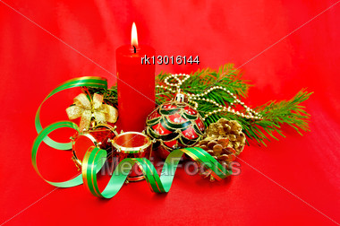 Red Burning Candle, Christmas Tree Decorations In The Form Of A Ball, A Hand Bell With A Bow, A Drum, Cones Against Red Silk Stock Photo