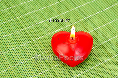 Red Candle In The Shape Of A Heart On A Green Bamboo Mat In The Bottom Right Corner Stock Photo