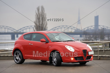 Red Car Parked On The Background Of The Bridge, Riga, Latvia Stock Photo