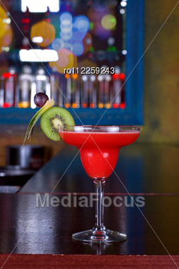 Red Cocktail With Kiwi On The Wooden Bar Stock Photo