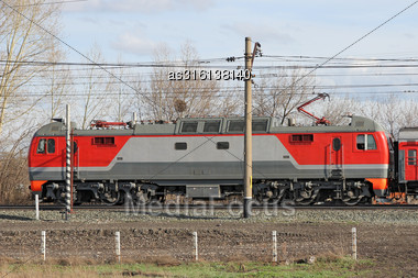 Red Locomotive On Electricity Coming By Rail Stock Photo