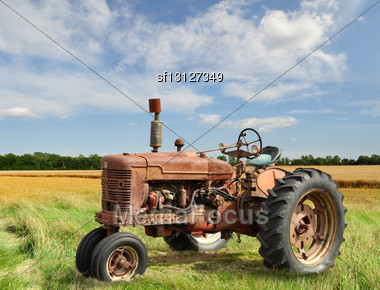 Red Old Rusty Tractor In A Field Stock Photo