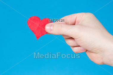 Red Paper Heart In Hand, Over A Blue Background Stock Photo