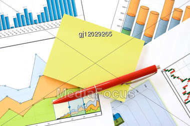Red Pen And Yellow Memo Over Financial Charts Stock Photo