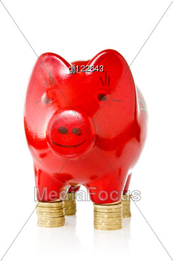 Red Piggy Bank Standing On Coins Stacks Stock Photo