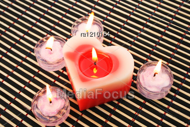 Red And Pink Candles On Wooden Math. Stock Photo