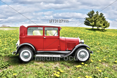 Red Retro Car On A Green Field Stock Photo