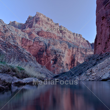 Red Rocks Of A Bluff Reflect Off The Colorado River In Grand Canyon National Park Near President Harding Rapid Stock Photo