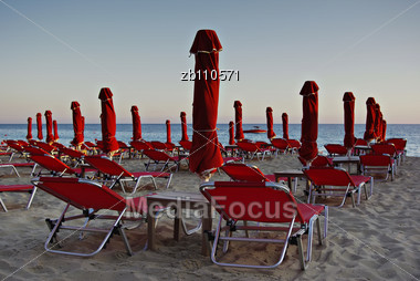 Red Sunshades And Sunbeds At Sandy Beach At Summer Sundown With Blue Sea And Sky In Background Stock Photo