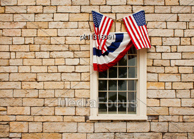 Red, White And Blue Bunting And Crossed American Flags Adorn A Casement Style Window Set In A Standstone Block Wall Stock Photo