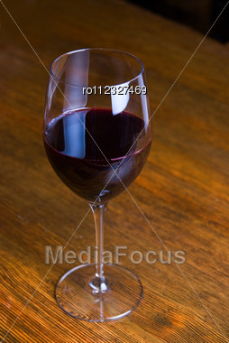 Red Wine Glass Over At Wooden Table Background Stock Photo