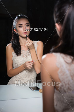 Reflection Of Attractive Young Brunette Doing Makeup Stock Photo