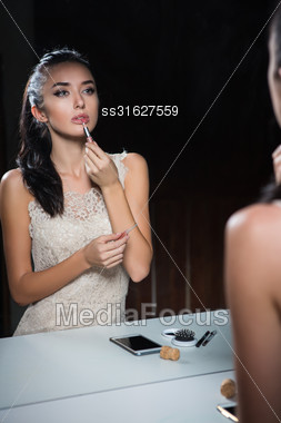 Reflection Of Beautiful Young Brunette Doing Makeup Stock Photo