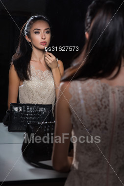 Reflection Of Cute Young Brunette Doing Makeup Stock Photo
