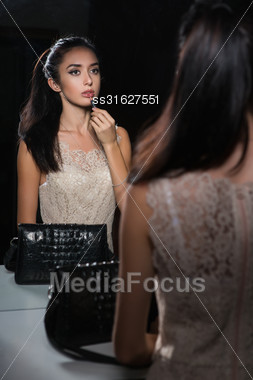 Reflection Of Nice Young Brunette Doing Makeup Stock Photo