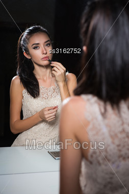 Reflection Of Pretty Young Brunette Doing Makeup Stock Photo