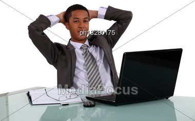 Relaxed Businessman Sitting At His Laptop Stock Photo