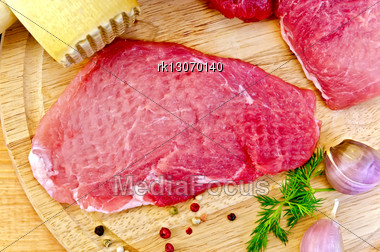 Repulsed A Piece Of Meat, Garlic, Pots Of Different Peppers, Fennel, Wooden Mallet On A Wooden Board Stock Photo
