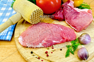 Repulsed A Piece Of Meat, Garlic, Pots Of Different Peppers, Fennel, Tomatoes, Sweet Pepper, Blue Napkin, A Wooden Mallet On A Wooden Board Stock Photo