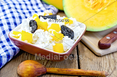 Rice With Caramelized Pumpkin, Prunes In A Clay Bowl, Raw Sliced Pumpkin, Green Napkin, Spoon On A Wooden Boards Background Stock Photo