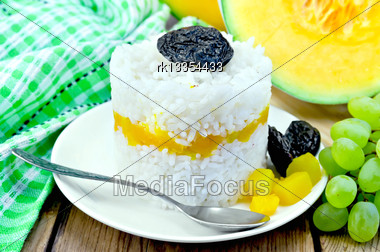 Rice With Caramelized Pumpkin, Prunes And Spoon On White Plate, Raw Sliced Pumpkin, Green Napkin, Grapes On A Wooden Board Stock Photo