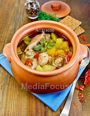 Roast With Chicken Meat, Potatoes And Red Pepper In A Clay Pot, Blue Napkin, Spoon, Crispbreads, Dill And Pepper In A Jar On A Wooden Board Stock Photo
